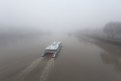 © Licensed to London News Pictures. 17/12/2016. LONDON, UK.  A boat sounds its fog horn as it travels on the River Thames this morning. London and the River Thames was shrouded in thick fog this morning.  Photo credit: Vickie Flores/LNP