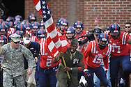Gunnery Sergeant LaTravis Wilcox carries the U.S. flag as he lead the Rebels onto the field before Ole Miss vs. Presbyterian at Vaught-Hemingway Stadium in Oxford, Miss. on Saturday, November 8, 2014. (AP Photo/Oxford Eagle, Bruce Newman)