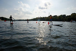 As the sun sets a small group of paddle-boarders make their way towards the performance area near the Strawberry Mansion Bridge. (Bastiaan Slabbers/for PhillyVoice)