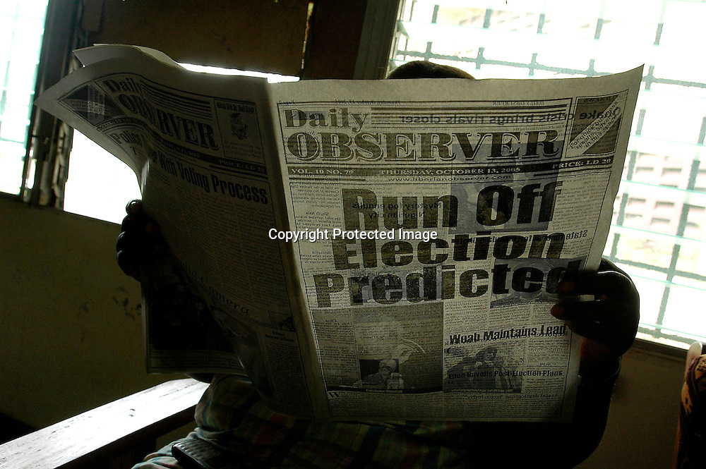 A woman reads a newspaper with a headline predicting a run-off in the country's presidential election, in Monrovia, Liberia, October 13, 2005.  Results from the Oct. 11 vote have been trickling in, and only 278 of 3070 polling places had reported their results as of the morning of Oct. 13.