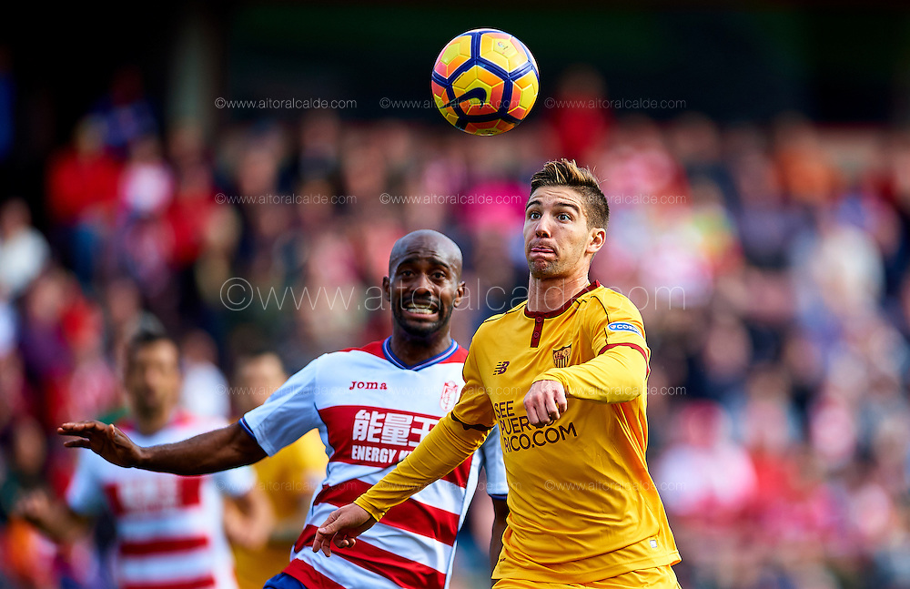 GRANADA, SPAIN - DECEMBER 03:  Luciano Vietto of Sevilla FC (R) competes for the ball with Dimitri Foulquier of Granada CF (L) during the La Liga match between Granada CF and Sevilla FC at Estadio Nuevos Los Carmenes on December 03, 2016 in Granada, Spain.  (Photo by Aitor Alcalde Colomer/Getty Images)