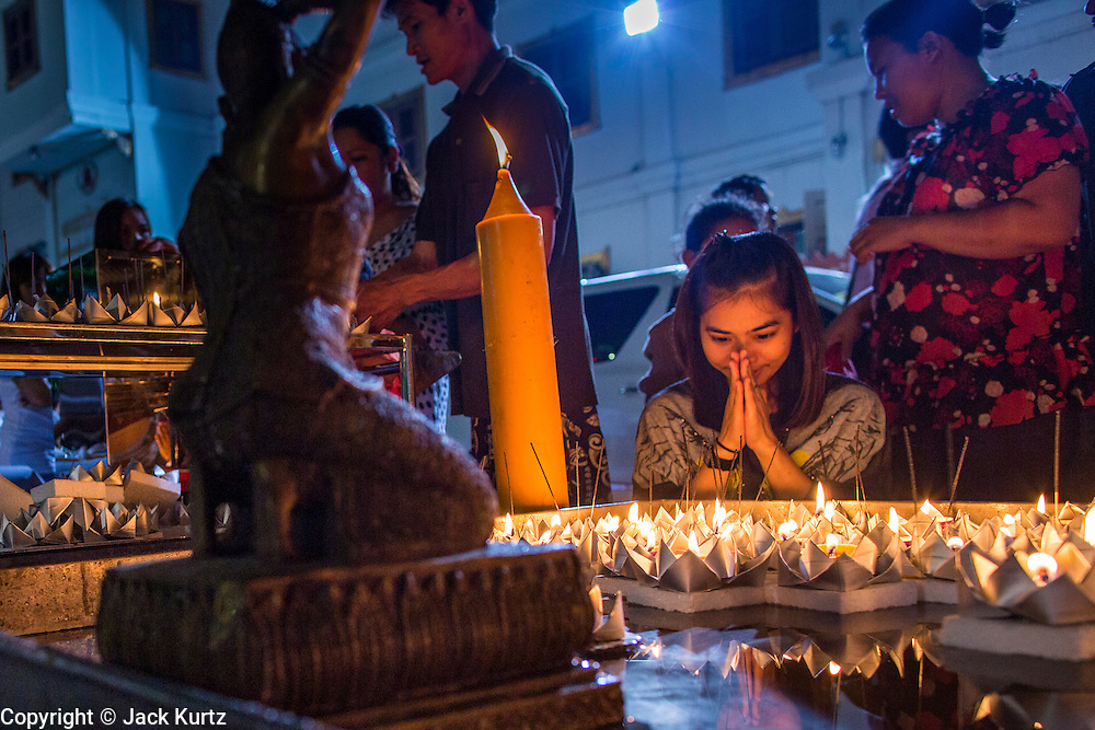 28 NOVEMBER 2012 - BANGKOK, THAILAND:  A woman prays at a small pool after floating her krathong at Wat Yannawa in Bangkok. Loy Krathong takes place on the evening of the full moon of the 12th month in the traditional Thai lunar calendar. In the western calendar this usually falls in November. Loy means 'to float', while krathong refers to the usually lotus-shaped container which floats on the water. Traditional krathongs are made of the layers of the trunk of a banana tree or a spider lily plant. Now, many people use krathongs of baked bread which disintegrate in the water and feed the fish. A krathong is decorated with elaborately folded banana leaves, incense sticks, and a candle. A small coin is sometimes included as an offering to the river spirits. On the night of the full moon, Thais launch their krathong on a river, canal or a pond, making a wish as they do so.   PHOTO BY JACK KURTZ