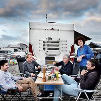 Nederland, Amsterdam , 1 oktober 2014.<br /> De rij caravans met mensen die een zelfbouwkavel willen kopen op het Zeeburgereiland wordt steeds groter.<br /> Sommige staan al een paar weken in de wachtrij totdat ze een kavel mogen kopen. Pas volgende week zaterdag gaan de kavels pas in de verkoop, maar wie weg gaat, verliest zijn plek in de rij.<br /> Een van de kampeerders staat er al een tijdje in zijn caravan: 'Ik ben hier behoorlijk vroeg gaan staan, want er is &eacute;&eacute;n kavel waar ik echt ge&iuml;ntresseerd in ben. Er hoeft er maar een eerder te zijn en dan ben je 'm kwijt.'<br /> De wachtende kopers vinden het best gezellig op het terrein: 'Je ontmoet een soort van je toekomstige buren als het zo doorgaat. Dat geeft een apart campinggevoel en we barbecuen samen.'<br /> Een probleempje, als je weggaat ben je je plek kwijt. 'Als je moet werken moet je zorgen dat er iemand anders op je plek zit. Ik had hier eerst helemaal geen zin in, maar het is toch wel een bizar avontuur.'<br /> Op de foto: s'Avonds wordt er voor elkaar gekookt en komen buren bij elkaar.<br /> Foto:Jean-Pierre Jans