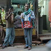 A hawker in the by lanes of Old Delhi selling chips out of a carry box. Old Delhi, May 2007