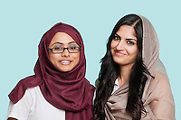Portrait of two happy young Muslim women in traditional clothing against blue background