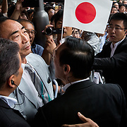 """TOKYO, JAPAN - JULY 1: Moritomo Gakuen head, Yasunori Kagoike (center), the academic organization linked to a land sale controversy that has engulfed Prime Minister Shinzo Abe and his wife Akie is surrounded by security members as he arrives at election campaign of main opposition, Liberal Democratic Party (LDP) in Akihabara, Tokyo, Japan on July 1, 2017. During the election campaign for Tokyo Metropolitan Assembly, anti-Abe protesters gathers chanting """"Abe wa Yamero!"""" """"Resign Prime Minister Abe!"""" during the campaign speech of PM Shinzo Abe and her candidate Aya Nakamura. (Photo: Richard Atrero de Guzman/NUR Photo)"""