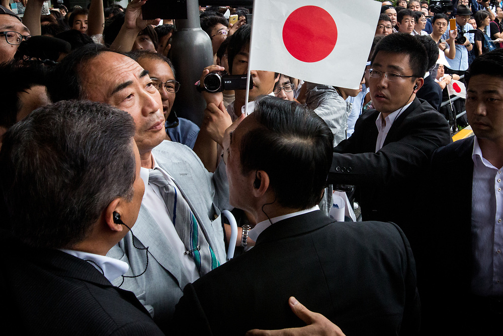 "TOKYO, JAPAN - JULY 1: Moritomo Gakuen head, Yasunori Kagoike (center), the academic organization linked to a land sale controversy that has engulfed Prime Minister Shinzo Abe and his wife Akie is surrounded by security members as he arrives at election campaign of main opposition, Liberal Democratic Party (LDP) in Akihabara, Tokyo, Japan on July 1, 2017. During the election campaign for Tokyo Metropolitan Assembly, anti-Abe protesters gathers chanting ""Abe wa Yamero!"" ""Resign Prime Minister Abe!"" during the campaign speech of PM Shinzo Abe and her candidate Aya Nakamura. (Photo: Richard Atrero de Guzman/NUR Photo)"