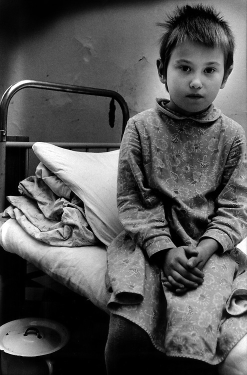 Young girl sitting alone on bed. TSIMBALINA HOSPITAL for abandoned children in NEVSKII RAYON area St Petersburg Russia. Children 2- 10 yrs spend 24 hours in quarantine to check for disease. They can stay for up to 6 months then go into children's home.
