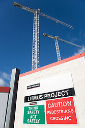 Shot looking up at cranes working on a new building; showing a 'Litmus Project' sign at ground level,  City of Nottingham,