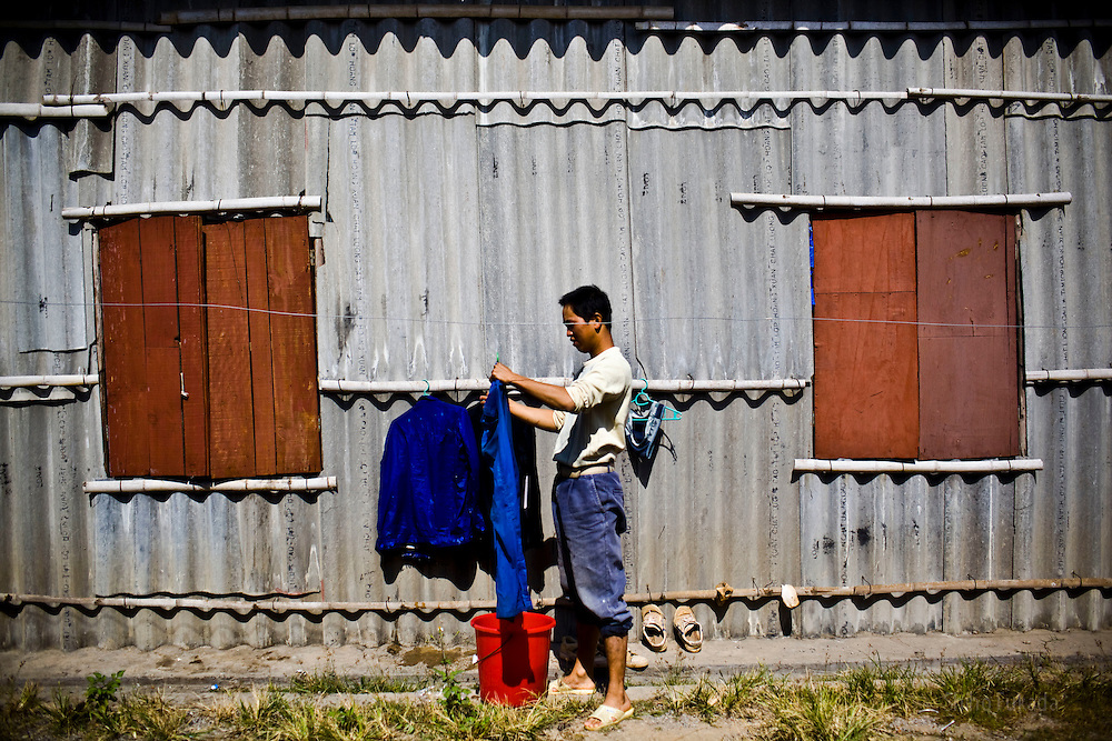A Chinese worker washes his clothes at the dorm near the Haiphong Thermal Power Plant construction site in Trung Son, Vietnam, Nov. 22, 2009. At the construction site here, a few miles northeast of the port city of Haiphong, an entire Chinese world has sprung up, including four walled dormitory compounds for the Chinese workers, restaurants with Chinese signs advertising dumplings and fried rice, and currency exchange shops.