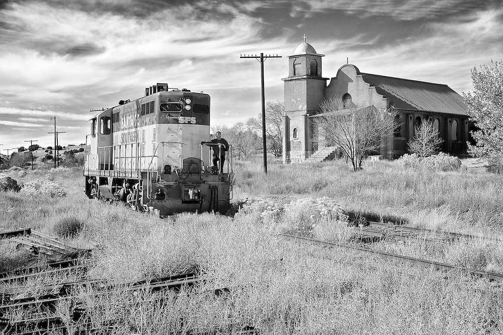 Having run around it's train, the engine passes the Mission Chapel of Our Lady of Light which closed in 1994. It opened in 1926 and was the only church ever constructed in Lamy which was once a thriving community on ATSF's main line and the junction for the connecting line into Santa Fe.