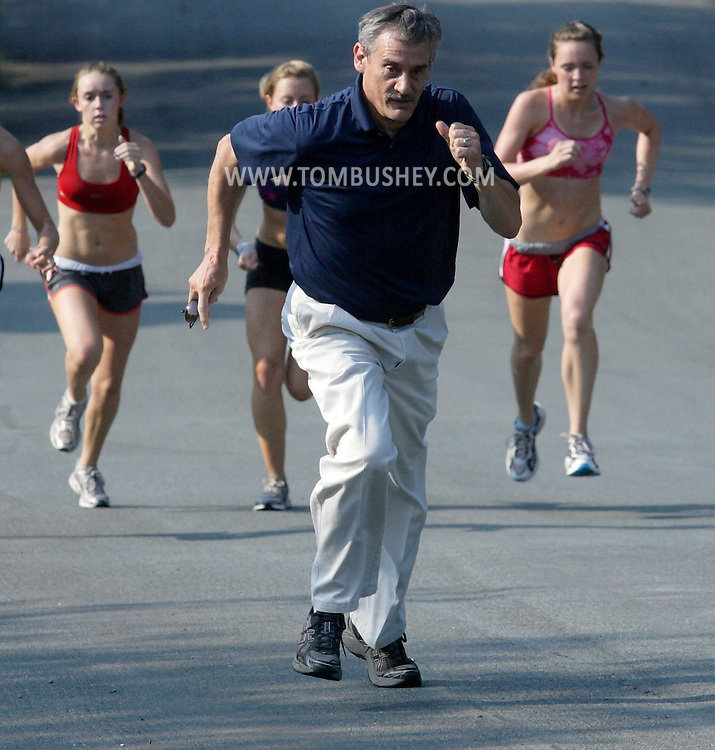 Warwick girls' cross country coach Rich Furst runs with his team during a hill workout on Wednesday, Sept. 1, 2010.