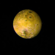 The trailing face of Jupiter's inner satellite Io is shown in this photo taken by Voyager 1 on March 3, 1979, from a distance of 1.7 million miles. A bright yellow-orange equatorial band (lower left to upper right) separates the darker reddish-brown polar zones. The north pole is at upper left. Characteristic of Io's surface is the profusion of dark spots commonly surrounded by rings of brighter material. The smallest dark spot visible in this view is 30 kilometres wide; the largest, on the left is about 400 kilometres across. The large heart-shaped feature with a dark spot near its centre could be Io's equivalent of an impact basin such as Mare Orientale on the Moon.