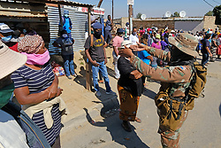 JOHANNESBURG, SOUTH AFRICA - MAY 08: An SANDF member instructs people to social distance outside a food distribution centre in Diepsloot on May 08, 2020 in Diepsloot, South Africa. In partnership with with government and Celebration Church, Engen Fuel Retailers contributed food parcels for over 4000 familes in Diepsloot during lockdown level 4. (Photo by Dino Lloyd)