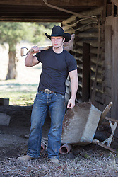 cowboy with a shovel over his shoulder standing by a barn