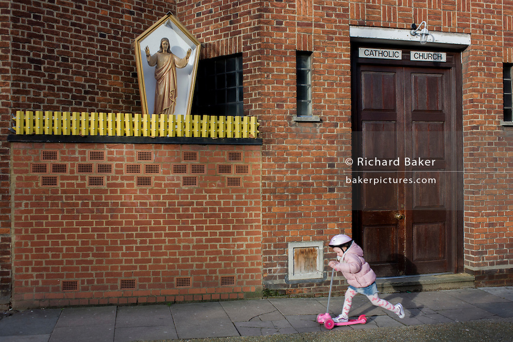 A young girl scoots beneath an effigy of Jesus Christ encased in a shrine box outside a Catholic church in Camberwell, south London.