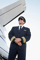 Pilot in uniform standing Beside an Airplane hands clasped low angle view