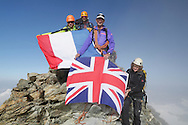 """British and French alpinists on the summit of Matterhorn.<br /> <br /> """"Matterhorn 150 years Cervino"""" - The year 2015 is the 150th Anniversary of the first ascent by Edward Whymper from the Swiss side (14th July) and by Jean Antoine Carrel from the Italian side on the 17th July 1865.<br /> <br /> On 17th July 2015 a friendship convention was signed by the members of Swiss, French, British and Italian climbing teams. A ceremony was held at the summit in honour of the mountain."""