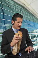 Businessman eating bagel while using laptop with earpiece in outside office building