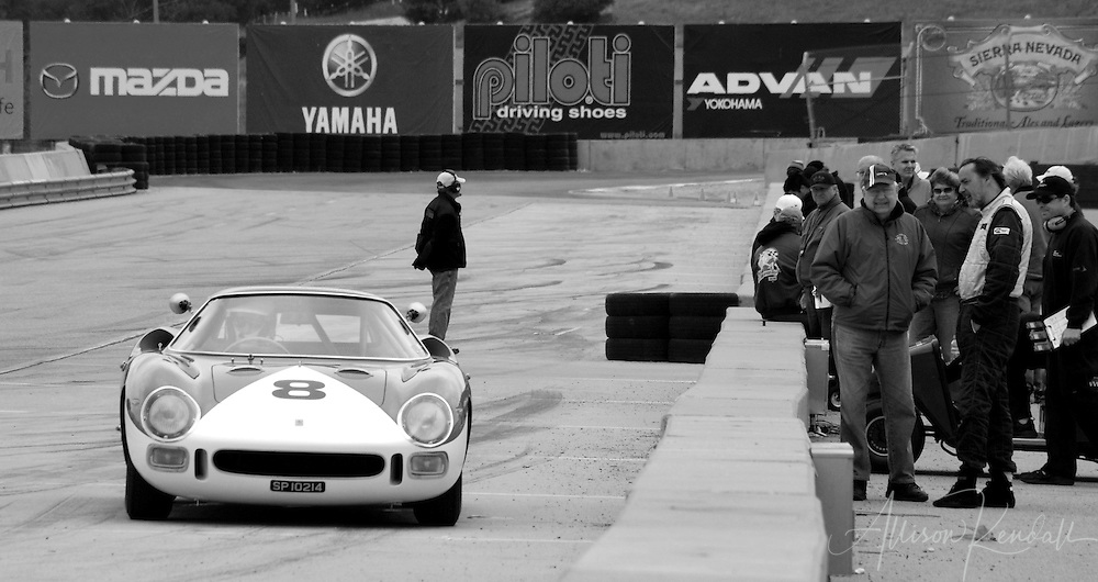 Drivers and crew mingle in the hotpits at Laguna Seca racetrack in Monterey, watching as a vintage racecar passes