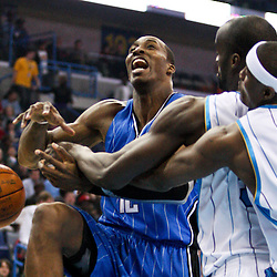 Feb 26, 2010; New Orleans, LA, USA; New Orleans Hornets center Emeka Okafor (50) fouls Orlando Magic center Dwight Howard (12) as forward James Posey (41) reaches in on the play during the first half at the New Orleans Arena. Mandatory Credit: Derick E. Hingle-US PRESSWIRE