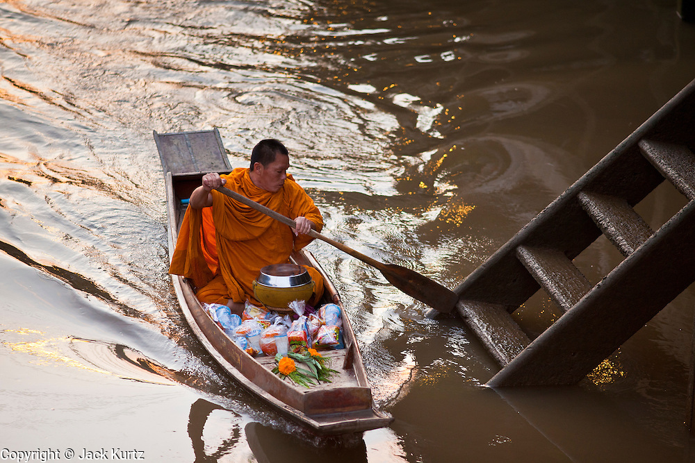 """10 JULY 2011 - AMPHAWA, SAMUT SONGKRAM, THAILAND:   A Buddhist monk from Wat Amphawan Chetiyaram in Amphawa, Thailand, about 90 minutes south of Bangkok, approaches a home on the main canal during his alms round. Most of the monks from the temple use boats to go from house to house on their alms rounds. The Thai countryside south of Bangkok is crisscrossed with canals, some large enough to accommodate small commercial boats and small barges, some barely large enough for a small canoe. People who live near the canals use them for everything from domestic water to transportation and fishing. Some, like the canals in Amphawa and nearby Damnoensaduak (also spelled Damnoen Saduak) are also relatively famous for their """"floating markets"""" where vendors set up their canoes and boats as floating shops.      PHOTO BY JACK KURTZ"""