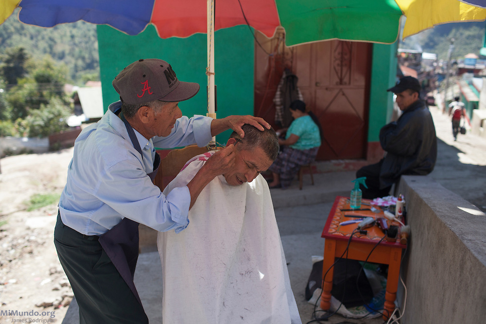 Felipe Juan (right) gets his haircut from Juan Tomás who carries out his business as a barber outside his home in the Santa Cecilia neighborhood. San Miguel Acatán, Huehuetenango, Guatemala. November 2, 2012.