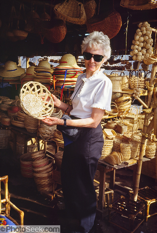 Mom shops for wicker wares (bowls, hats) at a market in Chile, South America.