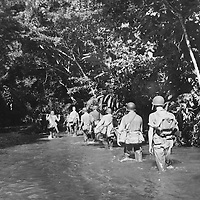 Marines march through the Tenaru River into the jungle on Guadalcanal in search of two Japanese 77mm field pieces. Their mission was accomplished.
