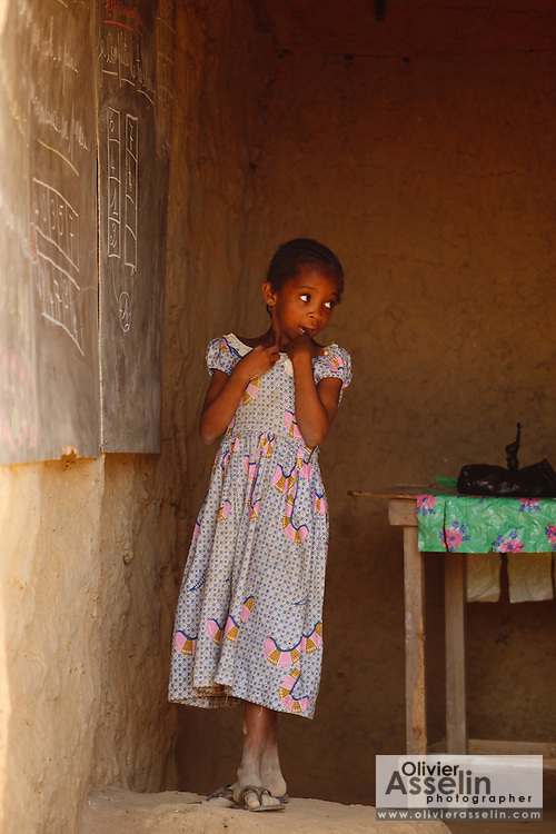 A girl stands by the blackboard in a private school in the village of Popoko, Bas-Sassandra region, Cote d'Ivoire on Tuesday March 6, 2012. A private school was opened after the public school reached it's maximum capacity.