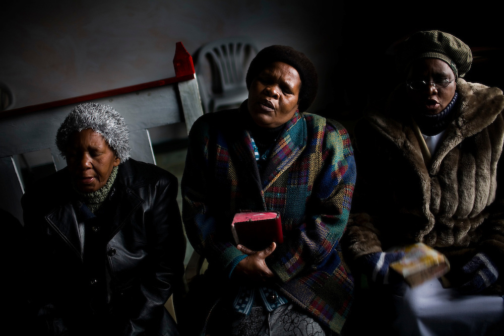 Women pray at the African Gospel Church. South African Gold miners are particularly vulnerable to contracting TB because of the small, poorly ventilated work conditions, high rates of TB and high rates of silicosis, a lung disease often found in miners that increases the chance of catching TB.