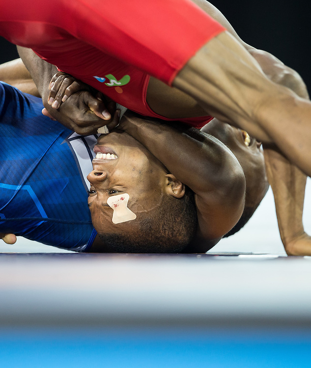 Andres Montano (L) of Ecuador vies for position with Spenser Mango of the United States during their semi-final bout in the 59kg class of the men's greco-roman wrestling  at the 2015 Pan American Games in Toronto, Canada, July 15,  2015.  AFP PHOTO/GEOFF ROBINS