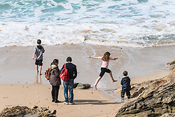 Adults and children on Fistral Beach in Newquay, Cornwall.