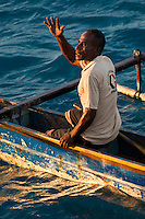 Fishermen in a traditional outrigger canoe, Mapia Atoll, West Papua, Indonesia.