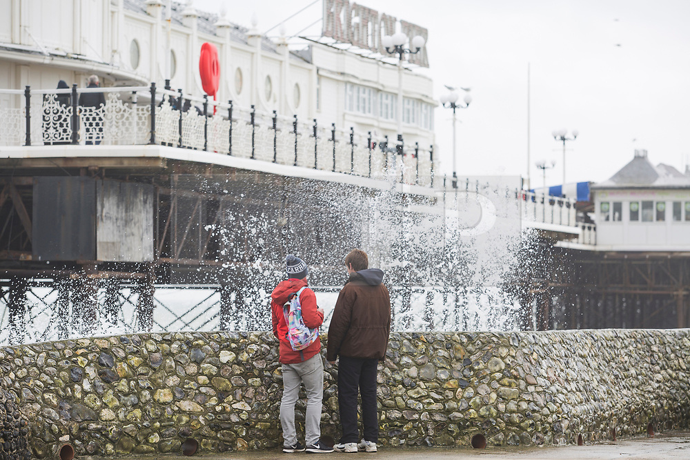 © Licensed to London News Pictures. 19/03/2017. Brighton, UK. Members of the public watching the waves that are crashing in to the pontoon next to the Brighton Palace Pier. Photo credit: Hugo Michiels/LNP