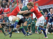 Frans Steyn of the Springboks is tackled by Jamie Heaslip and Ugo Monye of the Lions.<br /> Rugby - 090704 - Springboks vs British&Irish Lions - Coca-Cola Park - Johannesburg - South Africa. The Lions won the third test 28-9 but lost the series 2-1 to the Springboks.<br /> Photographer : Anton de Villiers / SASPA