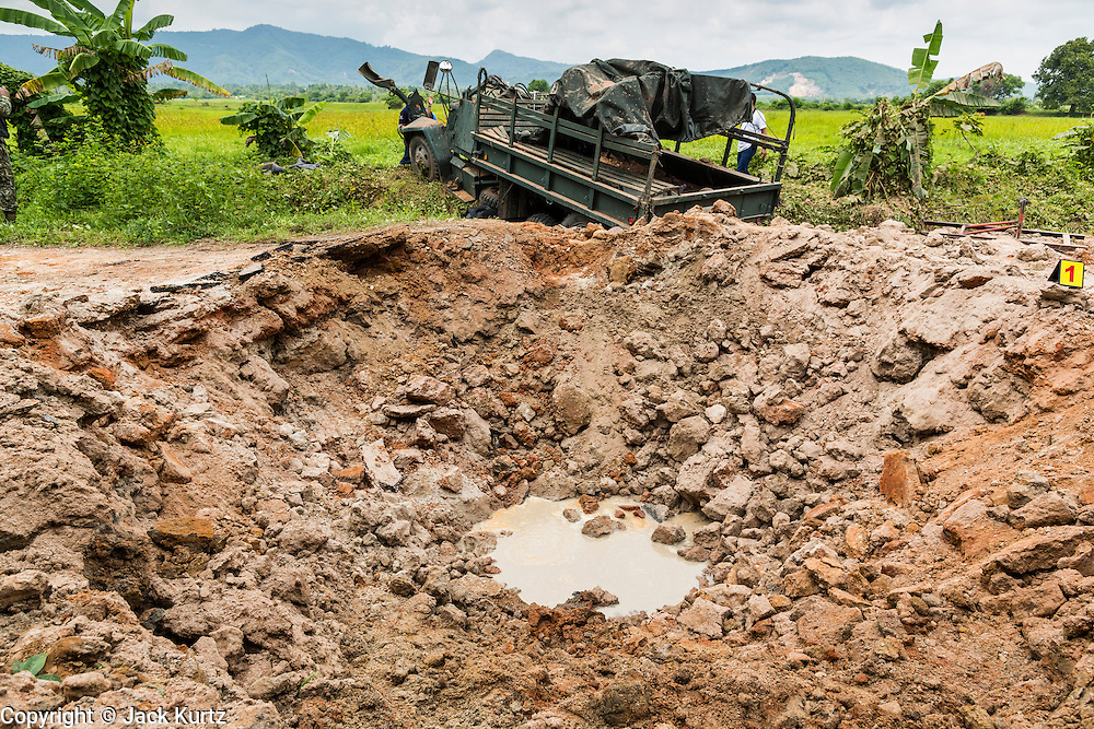 08 JULY 2013 - MAYO, PATTANI, THAILAND: The wrecked Thai army truck behind the crater created when an IED went off under the truck in Pattani Monday. Eight Thai soldiers were injured - one seriouly and seven with minor injuries - when their truck was hit by an IED outside Mayo, Pattani province in southern Thailand Monday. The soldiers were returning from a teacher protection mission when their truck ran over the explosive. The attack was thought to be conducted by Muslim insurgents who have been battling the Thai government for greater autonomy. The conflict in southern Thailand has claimed about 5,000 lives since 2004.    PHOTO BY JACK KURTZ