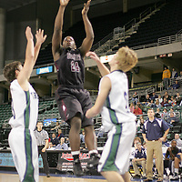 Falcon forward Alex Clark (24) launches a jumper against two wolves defenders.