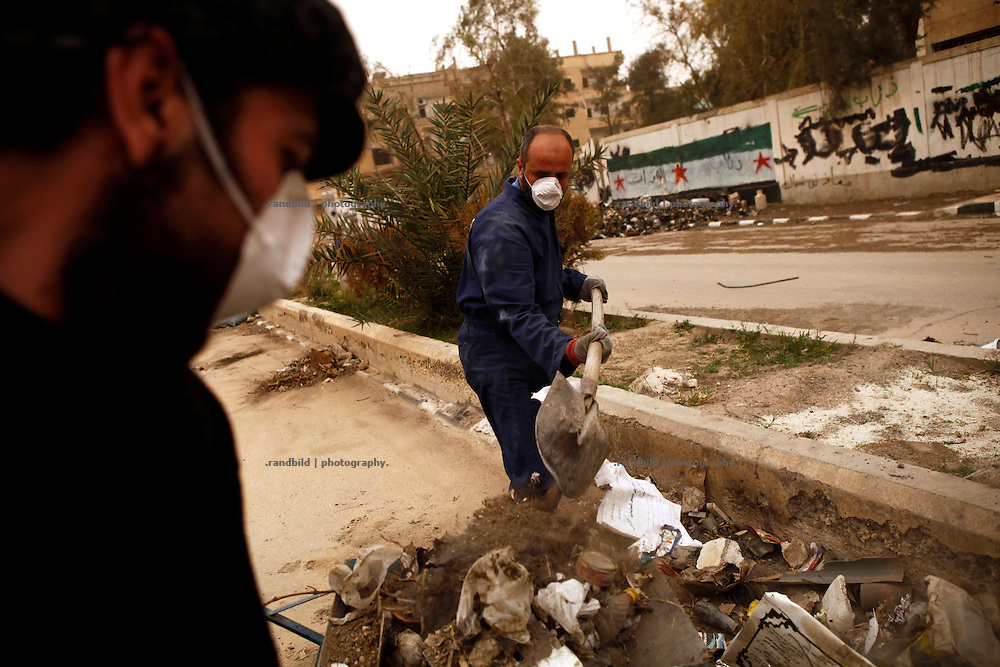 After weeks of firece fightings residents clean roads in Deir az-Zor from waste and debris. Residents of eastern syrian town Deir az-Zor joined arab spring protests against the regime of Bashar al-Assad from its early beginning in March 2011. Since summer 2012 the town with few hundred thousand inhabitants is embattled between the Syrian Army and different opposing rebel groups like Free Syrian Army and Jabhat al-Nusra. Deir az-Zor is target to constant shelling by artillery, war planes and short range missiles. Almost 70 percent of the town is rebel held while government forces remain in control over some residental areas and a strategic important airport. Deir az-Zor is widely damaged and some areas almost totally destroyed by fierce and long lasting battles. All direct road connections to Deir az-Zor are cut and fighters and returning residents as well depend on one provisional supply line across the Euphrates river which is regularly targeted by government snipers.