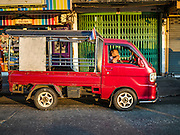 """30 DECEMBER 2015 - BANGKOK, THAILAND:  A """"songthaew,"""" a sort of home made bus that is used in small streets in Bangkok, waits for fares at Bang Chak Market. The market is supposed to close permanently on Dec 31, 2015. The Bang Chak Market serves the community around Sois 91-97 on Sukhumvit Road in the Bangkok suburbs. About half of the market has been torn down. Bangkok city authorities put up notices in late November that the market would be closed by January 1, 2016 and redevelopment would start shortly after that. Market vendors said condominiums are being built on the land.           PHOTO BY JACK KURTZ"""
