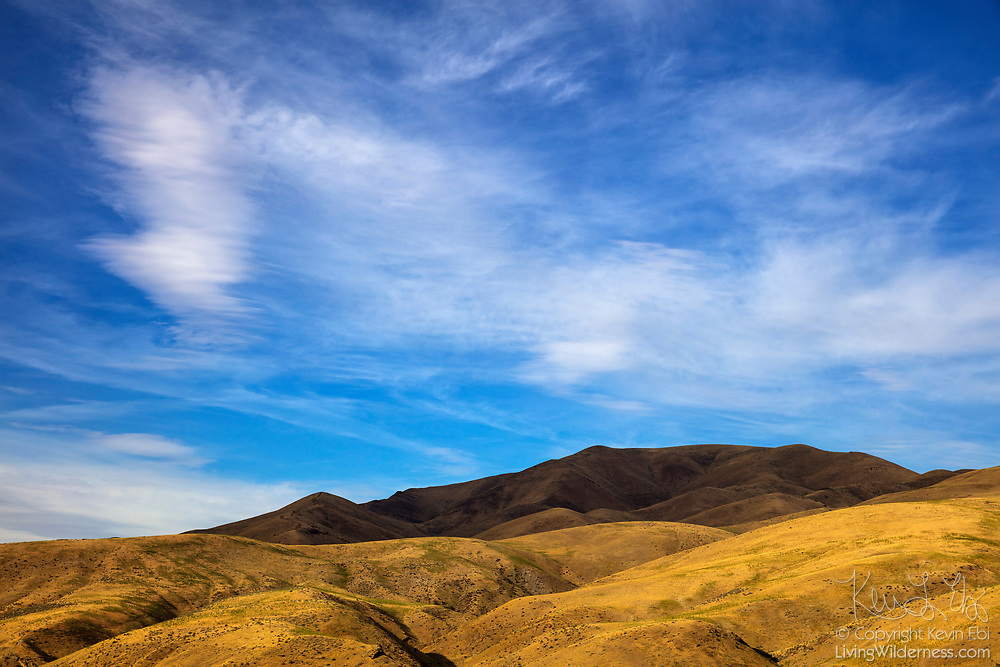 The summit of Dead Indian Ridge, located in Washington County Idaho, is in deep shadow as a band of altostratus clouds pass overhead in this view from near Huntington, Oregon.