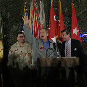 Pres. Bush, flanked by Gen. Ricardo Sanchez and Iraqi Administrator Paul Bremer, spends Thanksgiving dinner with troops of the 1st Armor Division in a mess hall at Baghdad International Airport Thursday, November 27, 2003.  In a clandestine night time move President Bush, with the knowledge of only a handful of senior staff, departed his ranch in Crawford, Texas and flew through the night to spend the Thanksgiving Day holiday visiting troops stationed in the war torn country...Photo by Khue Bui