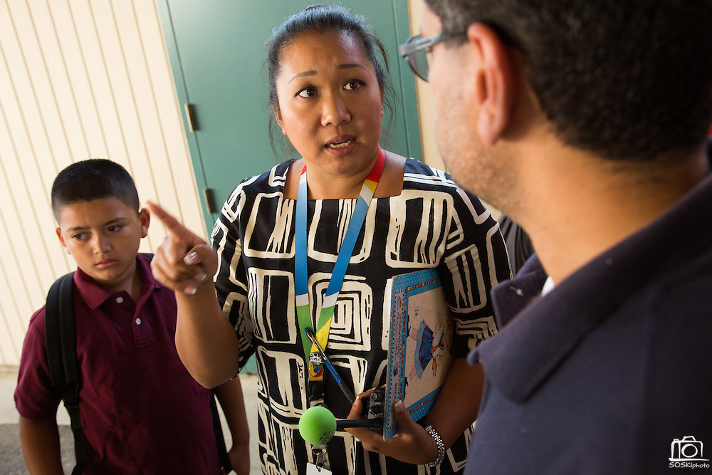 Principal Trisha Lee instructs parents about new before-school-student drop-off procedures during the first day of school at Zanker Elementary School in Milpitas, California, on August 19, 2013. (Stan Olszewski/SOSKIphoto)