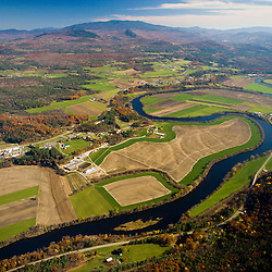 The Connecticut River flows through farmland in Newbury, Vermont and Haverhill, New Hampshire.  Mount Moosilaukee is in the distance. Aerial.