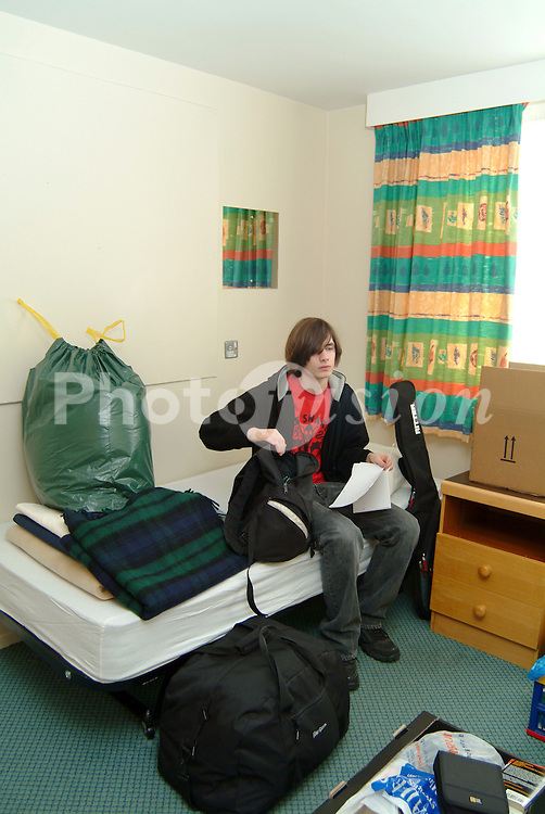 First year student unpacking his new Halls of Residence room at university UK