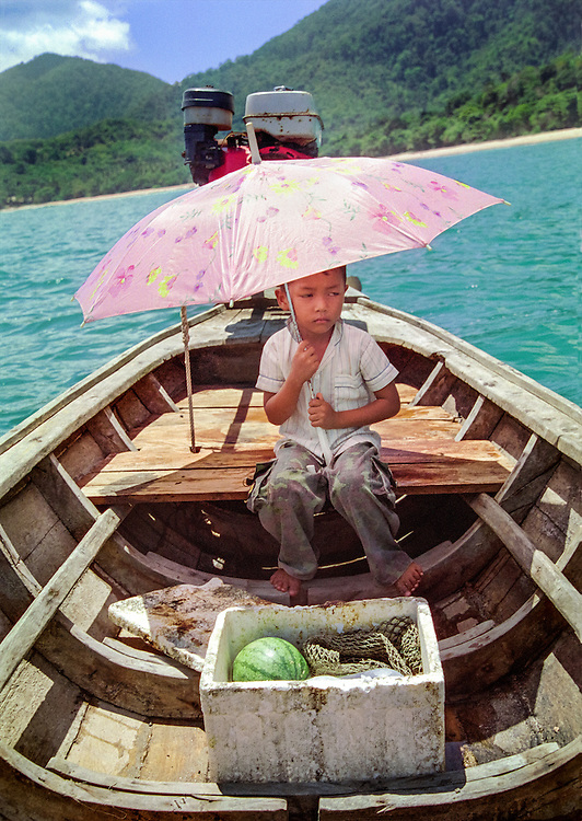 A young boy sheltering from the sun on his father's fishing boat in Ao Mai Pai, on the island of Koh Lanta, 2003.