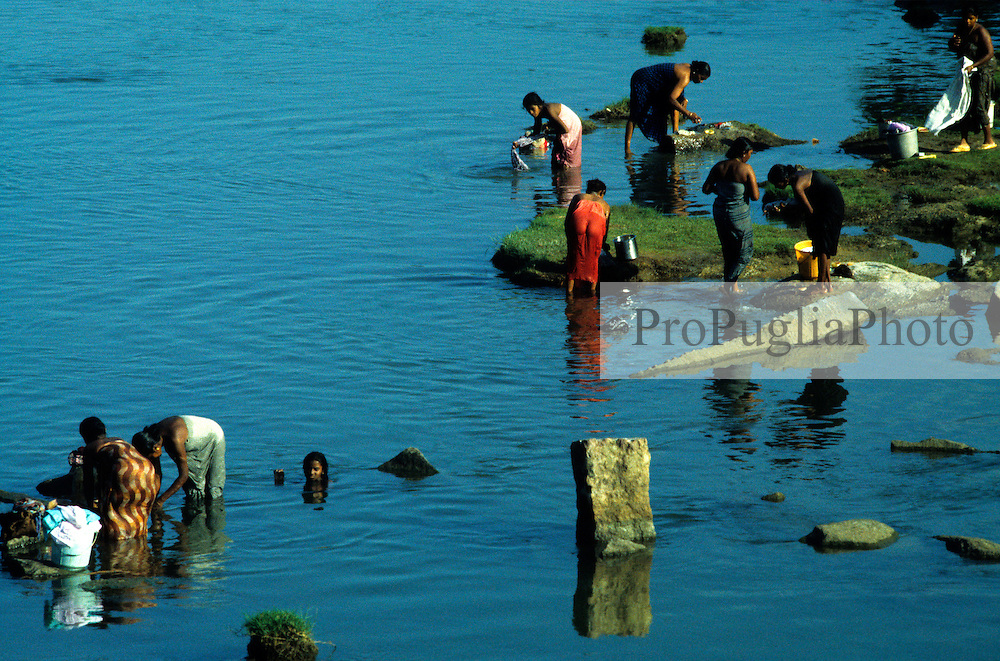 Kenyakumary, India 1994. Women washing their clothes while having a bath in a local lake.
