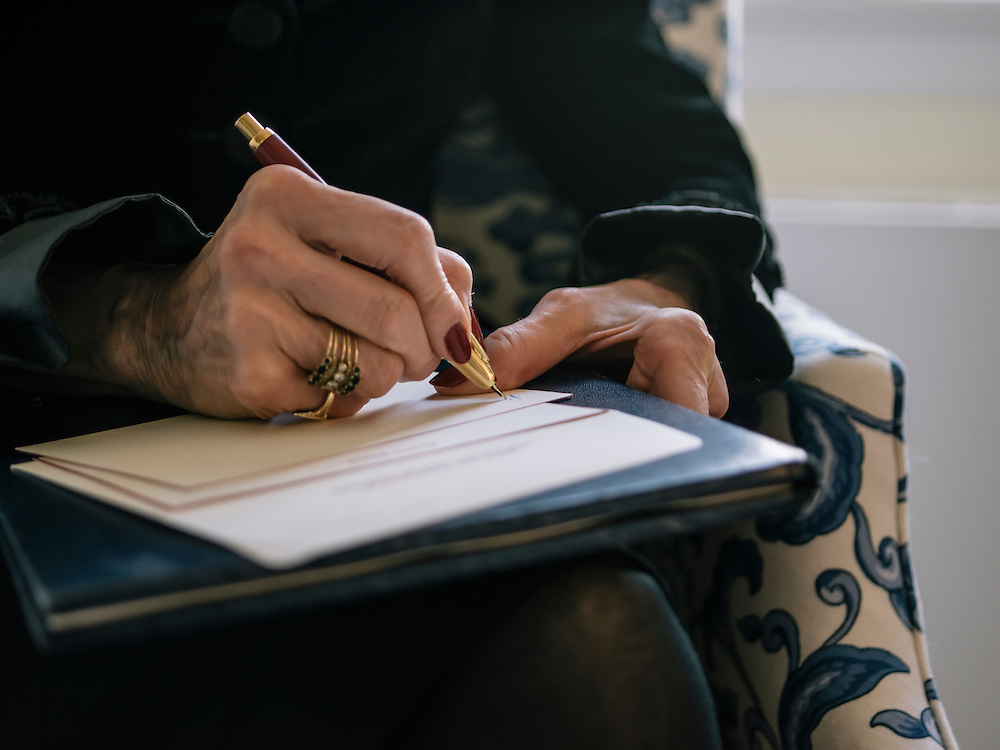 Diane Rehm writes a letter at her home on the 14th floor of a condominium complex in the Glover Park area of Washington, D.C.