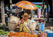 Woman under umbrella selling vegetables at local market in Inle Lake (Myanmar)