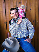 At an exotic animal auction, a cowboy in Missouri poses with a capuchin monkey, whose owner dresses her in American Girl doll clothes.